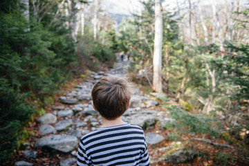 Boy looks forward towards a mountain hiking trail