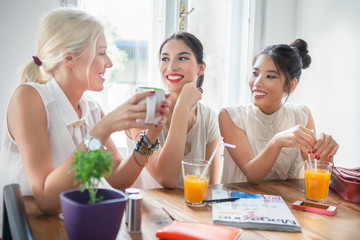 Smiling Women Chatting at a Cafe