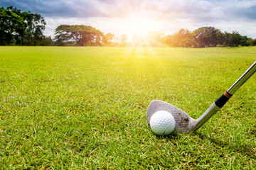 Golf club and golf ball in grass in sunrise.