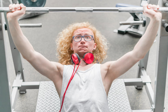 Curly blond man in a white vest lifting barbell with a strained face