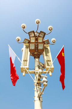 tall square lights and flags in front if Tiananmen