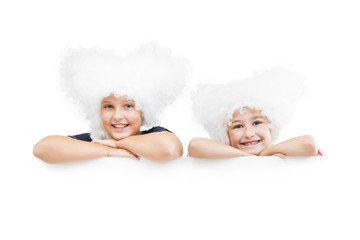 Smiling happy two young girls in white wigs  look out from the empty banner.