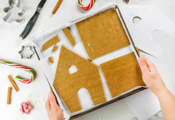 Preparing for Christmas, a person, hands in the frame, makes a gingerbread house. The girl is holding a baking tray with dough in the form of house details, ornaments in the frame. top view