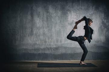 Beautiful sporty fit yogi woman practices yoga asana Natarajasana - Lord Of The Dance pose in the dark hall