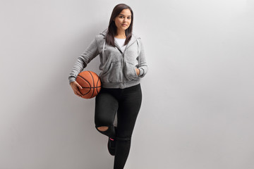 Teenage girl with a basketball leaning against a wall