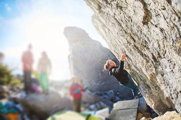 female rock climber climbs on a rocky wall. winter bouldering session