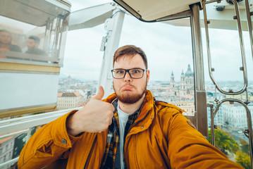 man at Ferris wheel taking a selfie