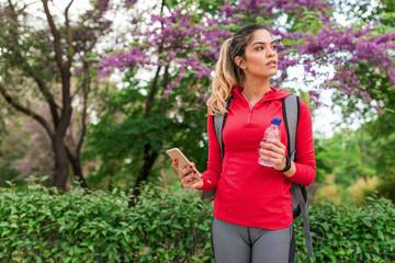 Sportive girl in park browsing smartphone