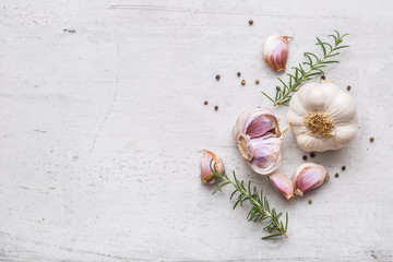 Garlic. Garlic bulbs. Fresh garlic with rosemary and pepper on white concrete board