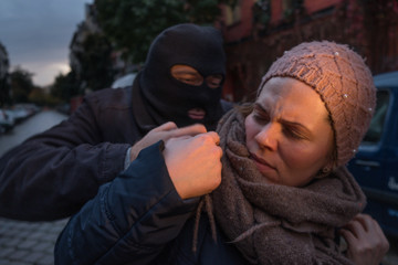 Unrecognizable masked man assaulting a woman