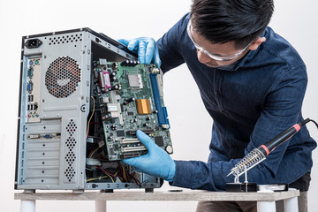 The technician put the computer mainboard in the computer case. the concept of computer hardware, repairing, upgrade and technology.