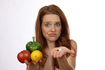 Hübsche rothaarige Frau mit Obst, Früchten und Tabletten schaut ratlos