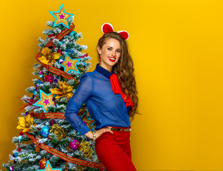 smiling woman standing near Christmas tree on yellow background