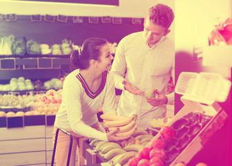 Positive couple choosing various fruits