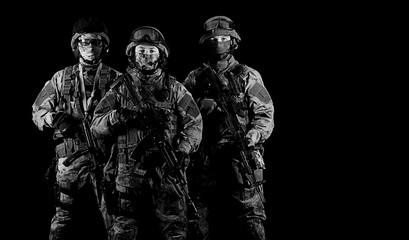 Three soldiers in uniform with a weapon in their hands are looking menacingly.