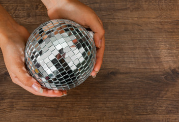 Female hand holding a shiny silver mirror disco ball on wooden background. with copy space. top view