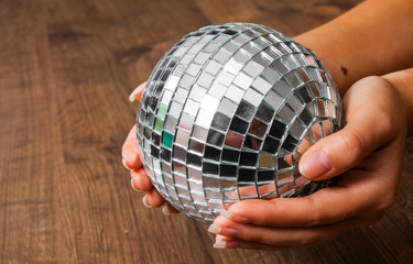Female hand holding a shiny silver mirror disco ball on wooden background. with copy space.