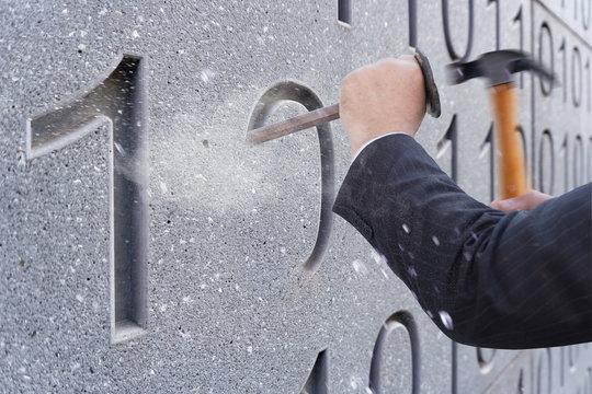 Nullen und Einsen werden in einer Betonwand gemeiselt -