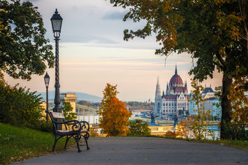 Budapest, Hungary - Bench and autumn foliage on the Buda hill with the Hungarian Parliament and Chain Bridge at background