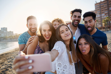 Group of friends taking selfie together on beach
