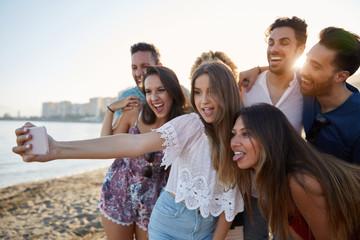Pretty girl taking selfie with friends on beach