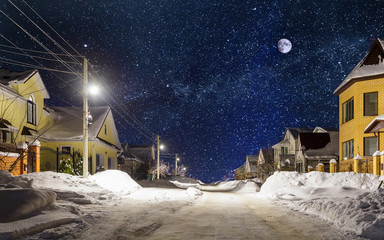 The stars and moon over a snowy village street.
