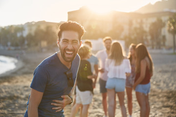 Young man standing on beach with friends laughing