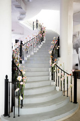 Staircase decorated with pink and white flowers