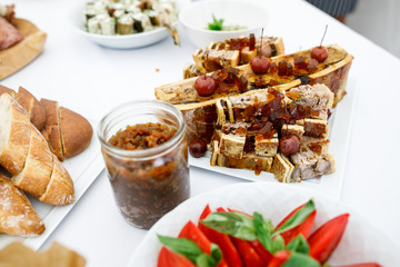 Plates with bread, vegetables, sliced meat and other snacks