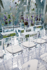 Ice cubes with violet flowers inside  stand before transparent plastic chairs ready for wedding ceremony