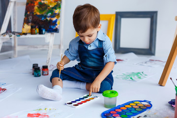 Cute, happy, white boy in blue shirt and jeans draws with paints among pictures and easels. Little child in studio painting with brush. Concept of early childhood education, happy family, parenting