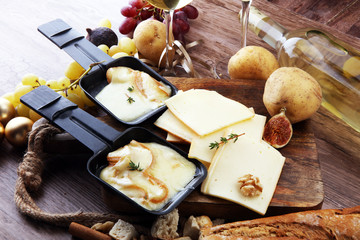 Delicious traditional Swiss melted raclette cheese on diced boiled or baked potato served in individual skillets