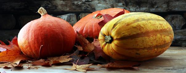 Thanksgiving background: pumpkins and fallen leaves on wooden background. Halloween, Thanksgiving day or seasonal autumnal