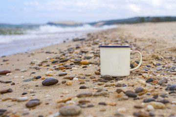 Enameled camp mug on the pebbles of the sandy shore of Lake Baikal during a wave on a mountain background in the summer on a clear sunny day.