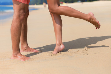 Legs of a kissing couple on a sea beach