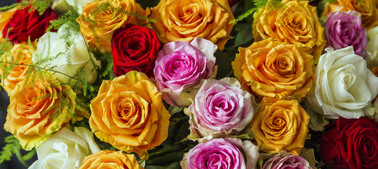 A beautiful and colorful bouquet of big roses in different colors in white paper with a black velvet background