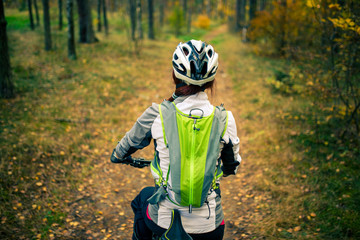 Image from back of woman in helmet on bicycle