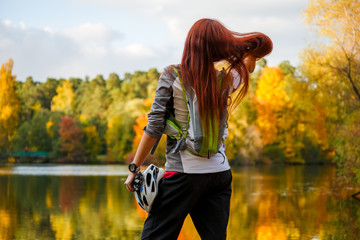 Photo from back of woman with backpack and bicycle helmet