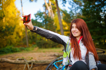 Image of happy girl photographing herself in autumn forest