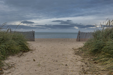 Beach path leading past grass and wooden fence