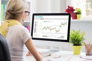 Woman trading currencies online on forex trading platform.