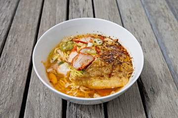 Egg noodle soup with roasted pork and crispy wonton, Thai style spicy noodle soup on wood background