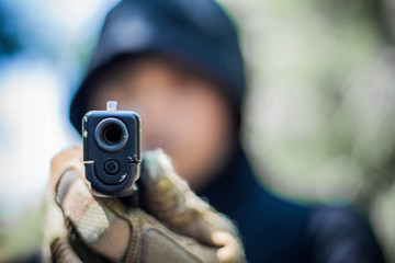 Terrorist or gunman wearing a mask and holding a gun ready to fire