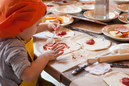 boy making homemade pizza working in the kitchen in chefs uniforms and smear sauce the base