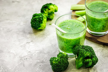 Green vegetable smoothie in glass at gray background