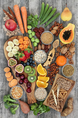 Health food concept for a high fibre diet with fruit, vegetables, cereals, nuts, seeds, whole wheat...