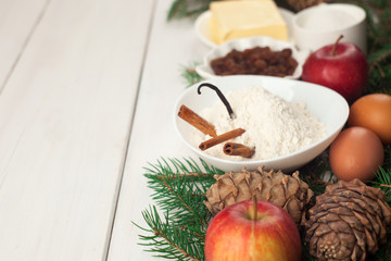 Baking ingredients. eggs, butter, spice, apples, raisins, vanilla and cinnamon sticks, white flour and xmas tree on white wooden table background. copy space, new year, xmas, food concept