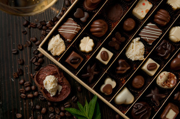 chocolate box of pralines perfect gift for a romantic dinner. Glass of white wine and coffee beans on a wood table and a mint