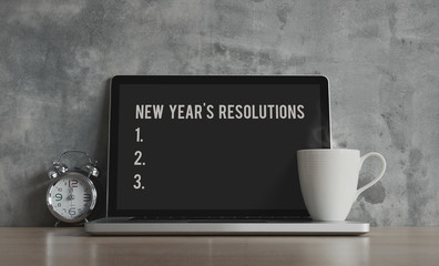 New Year resolutions, notes, goals, post, memo or action plan concept. Blank monitor for input text on laptop in workplace office with clock and coffee on wooden desk and loft wall.