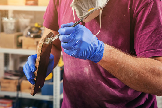 A close-up of a male carpenter in a purple t-shirt and disposable blue gloves gently paints a wooden tassel with a wooden block in a dark brown color in the workshop